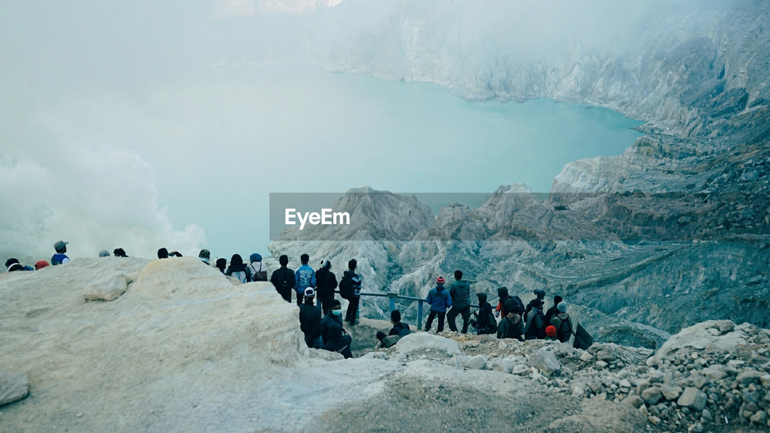 People standing on observation point against rocky mountains