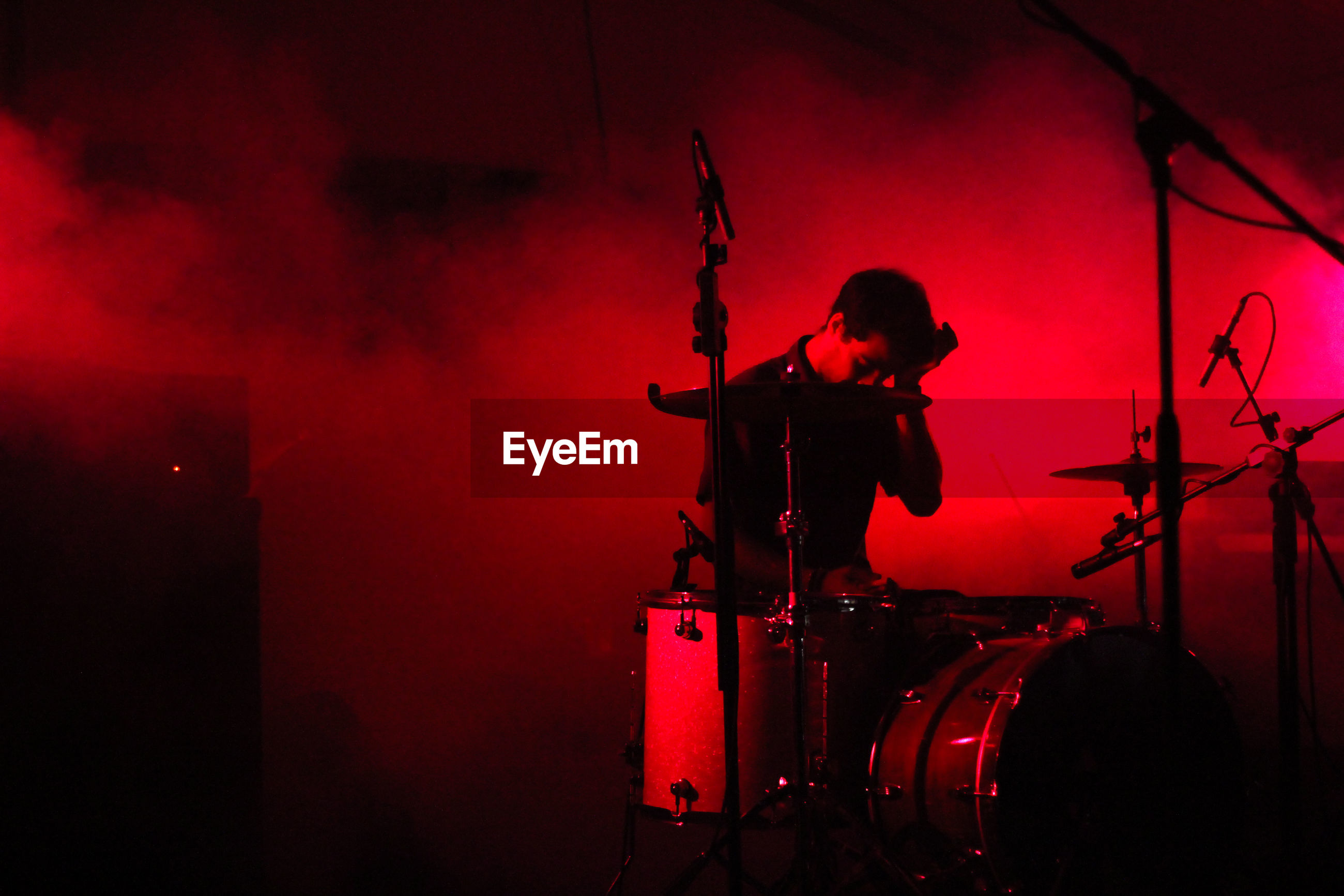 Drummer sitting by drums during music concert