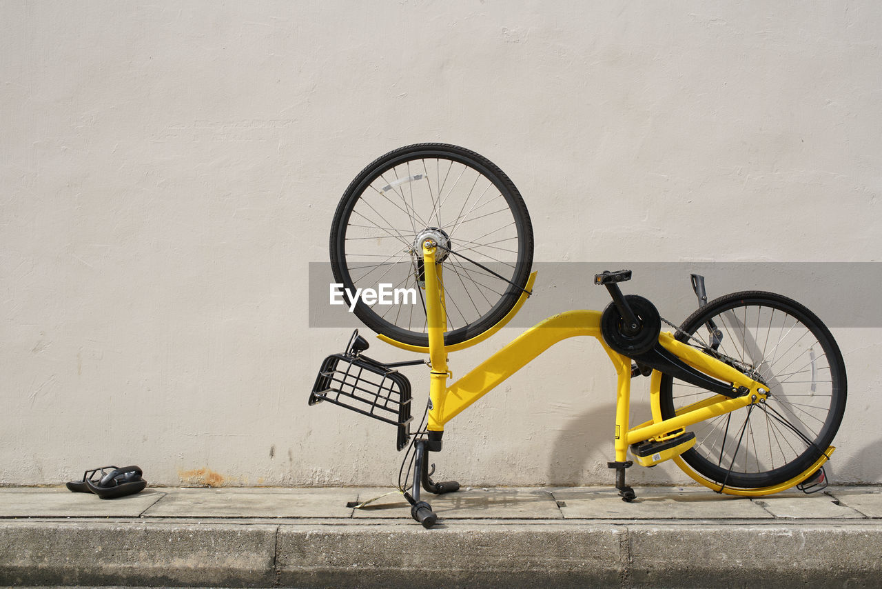 bicycle, transportation, mode of transportation, land vehicle, wheel, wall - building feature, stationary, architecture, no people, day, city, built structure, street, outdoors, yellow, sidewalk, footpath, parking, travel, wall, tire