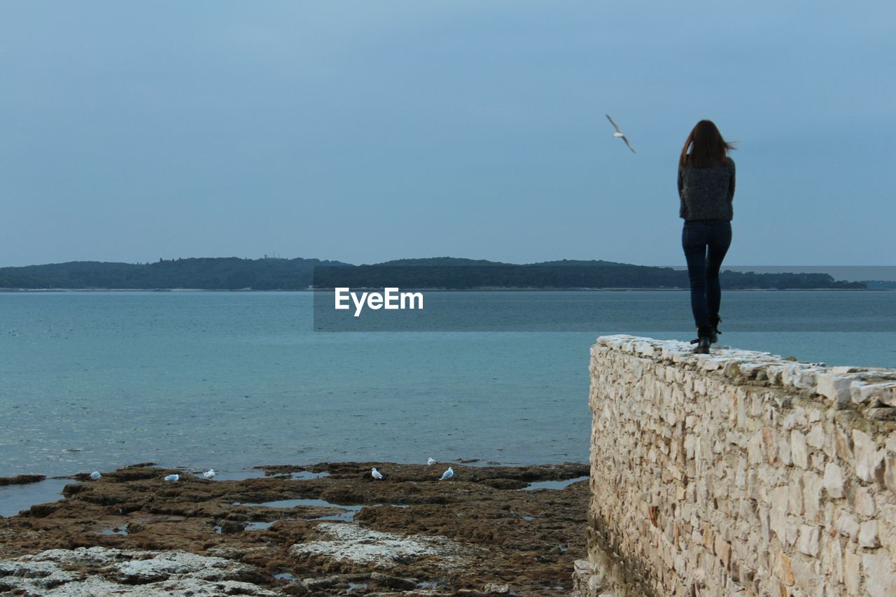 water, sea, rear view, real people, nature, standing, beauty in nature, scenics, one person, outdoors, day, tranquility, lifestyles, men, horizon over water, full length, women, clear sky, sky, people