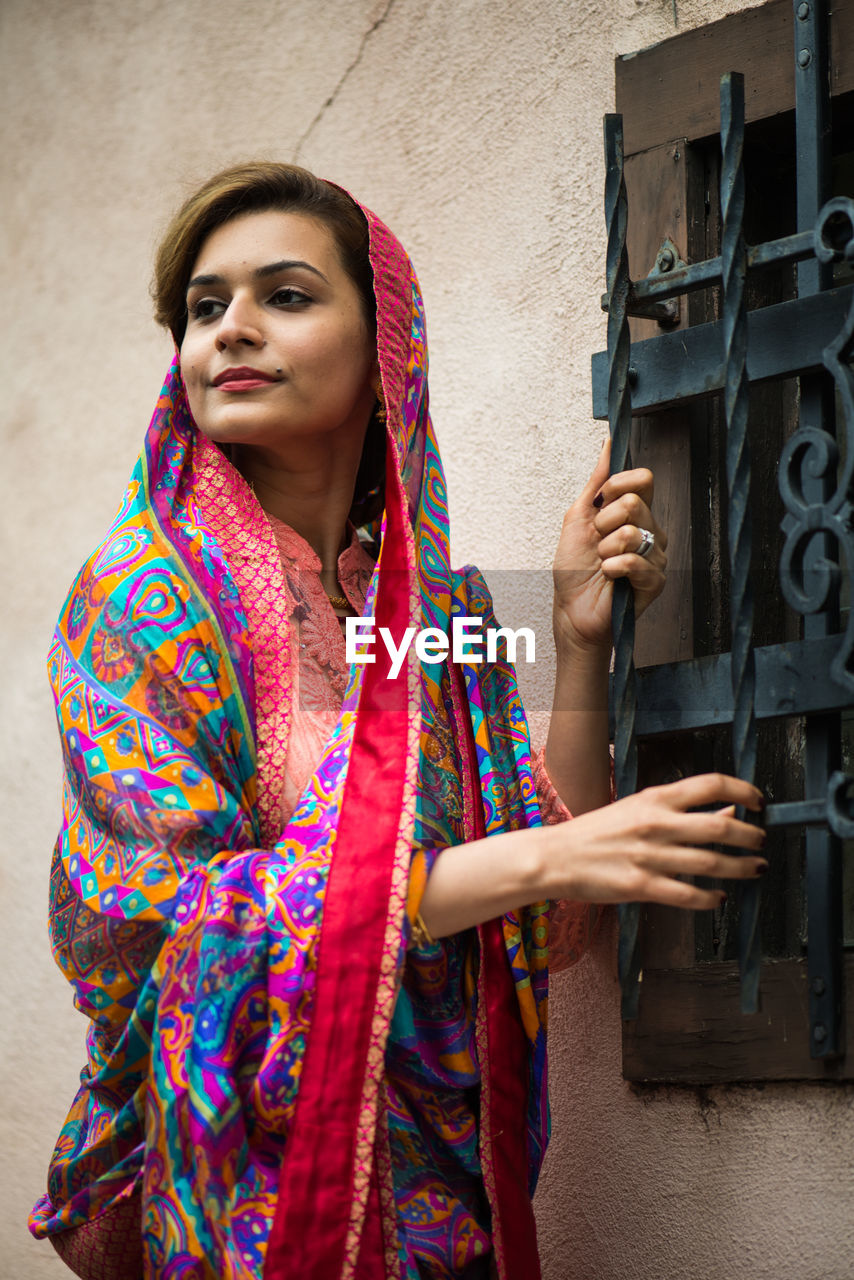 Confident beautiful woman in traditional cloths standing against wall