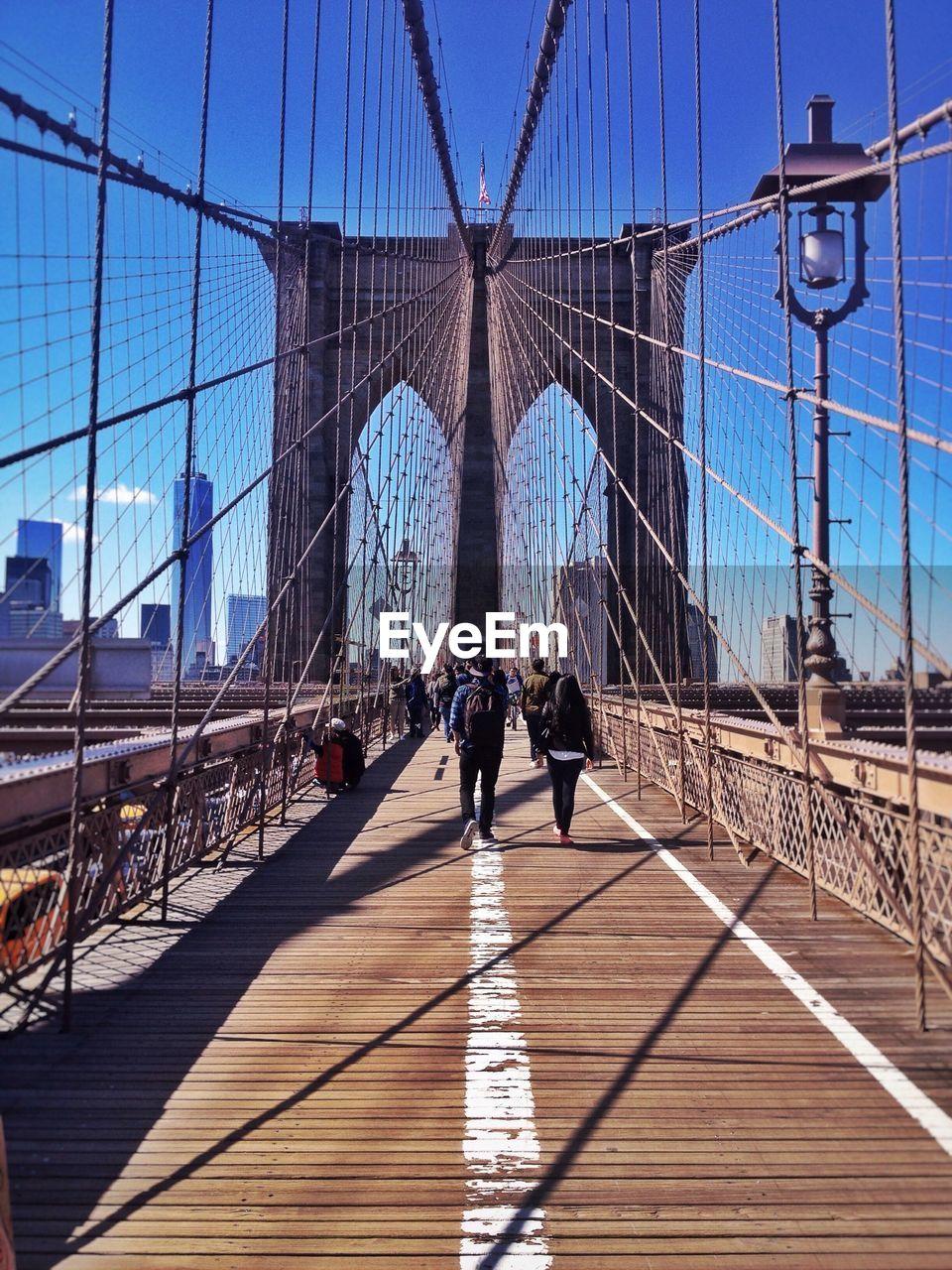 People Walking On Brooklyn Bridge Against Blue Sky