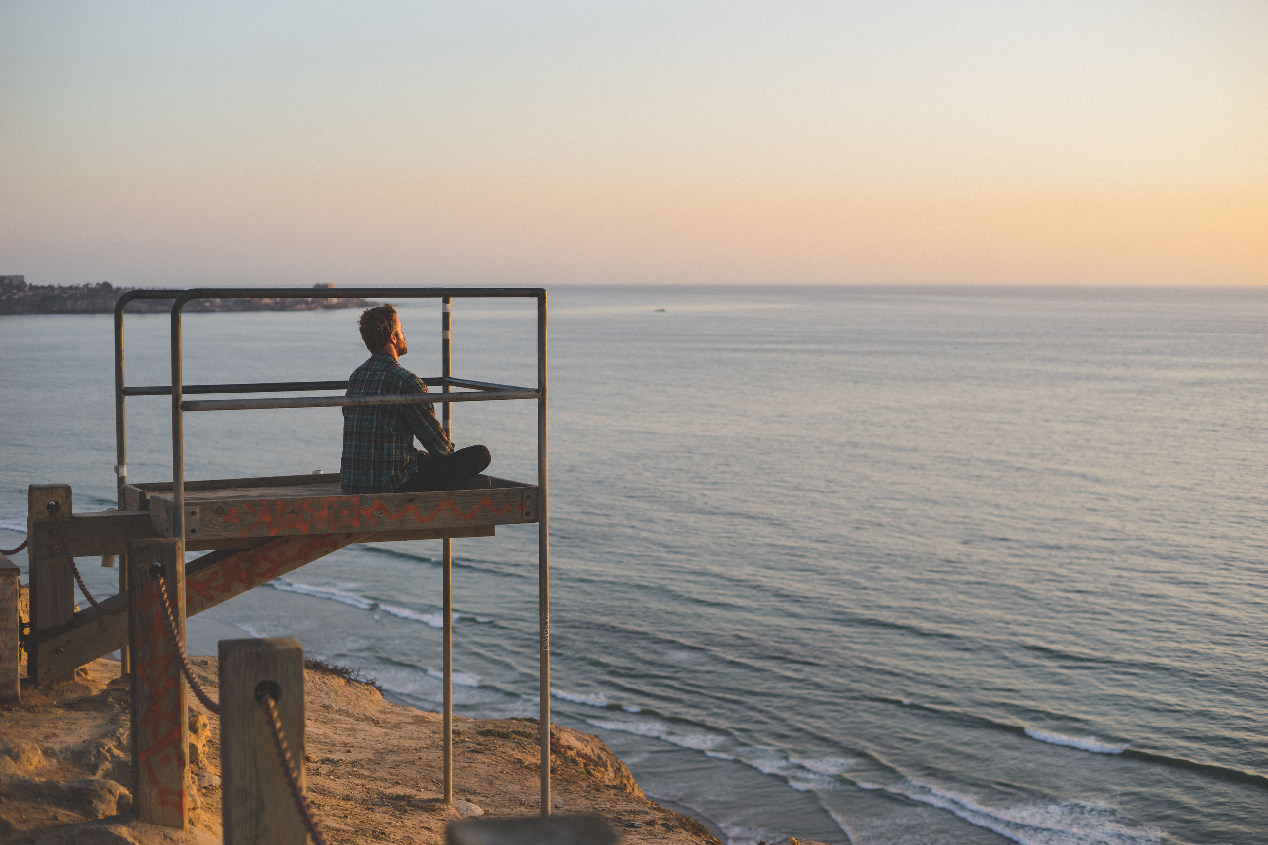 MAN FISHING AT SEA SHORE AGAINST CLEAR SKY