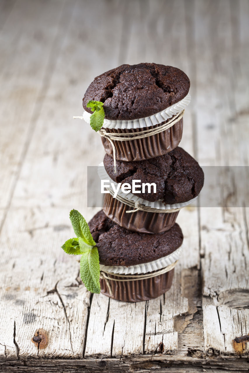 wood - material, food and drink, still life, food, freshness, indoors, no people, table, sweet food, focus on foreground, chocolate, cupcake, close-up, indulgence, dessert, sweet, temptation, unhealthy eating, cake, brown, muffin, cupcake holder, chocolate cake