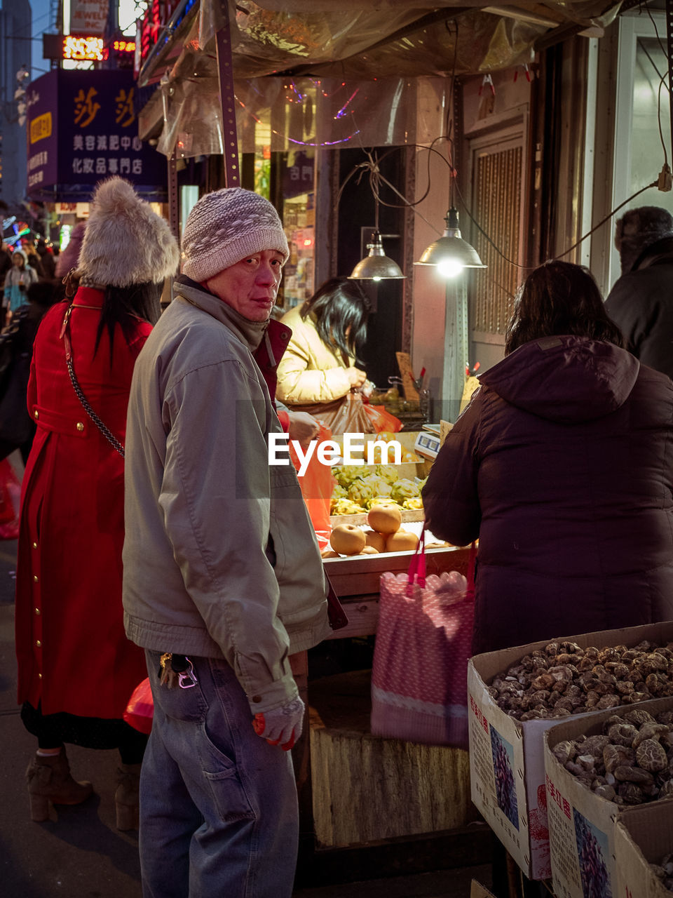 real people, women, market, adult, men, clothing, retail, three quarter length, winter, warm clothing, lifestyles, leisure activity, market stall, rear view, incidental people, group of people, shopping, people, illuminated, for sale, buying, retail display, sale
