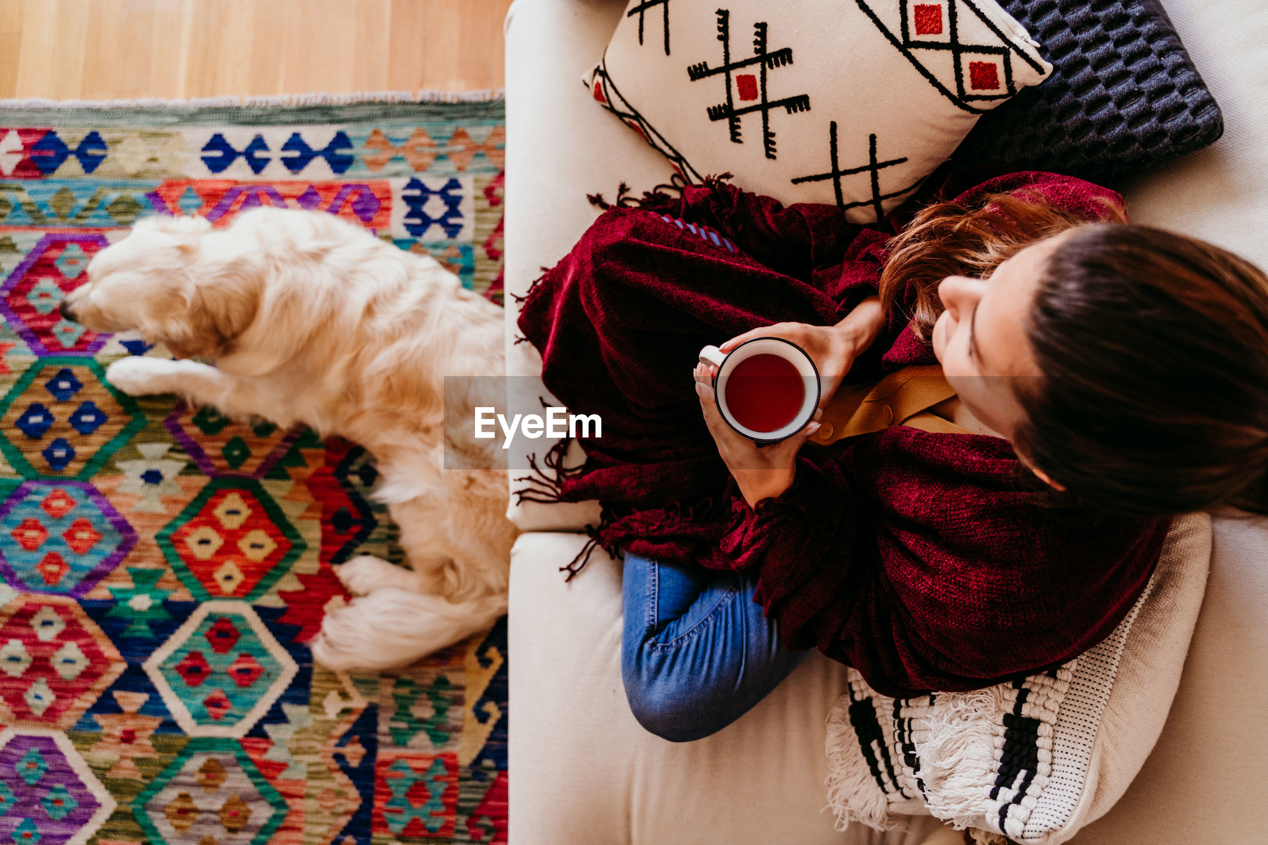 High angle view of woman holding coffee cup while sitting on sofa by dog at home