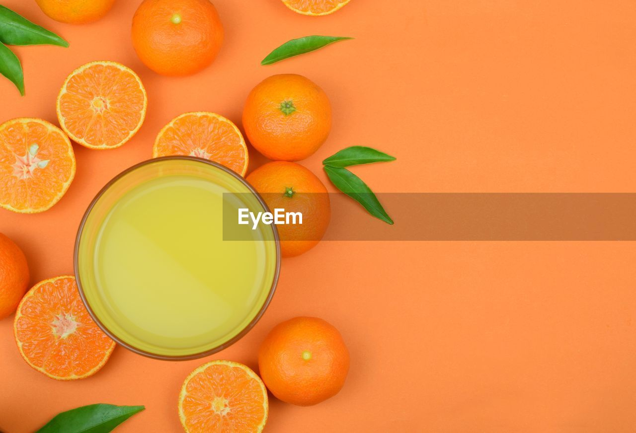 healthy eating, wellbeing, orange color, food, food and drink, fruit, orange - fruit, freshness, orange, still life, indoors, citrus fruit, directly above, studio shot, copy space, no people, high angle view, large group of objects, colored background, cross section, orange background, ripe