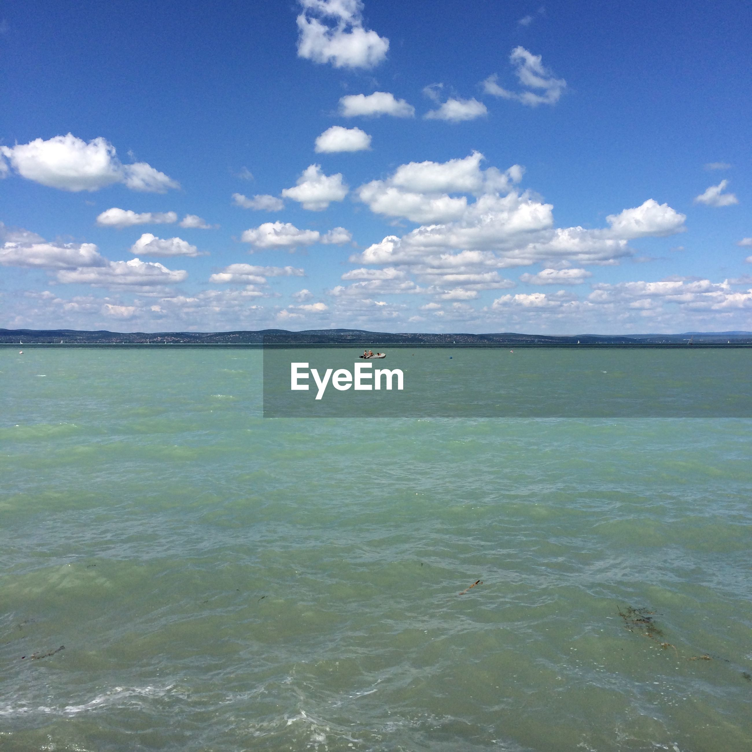 Distant view of people in lake balaton against sky