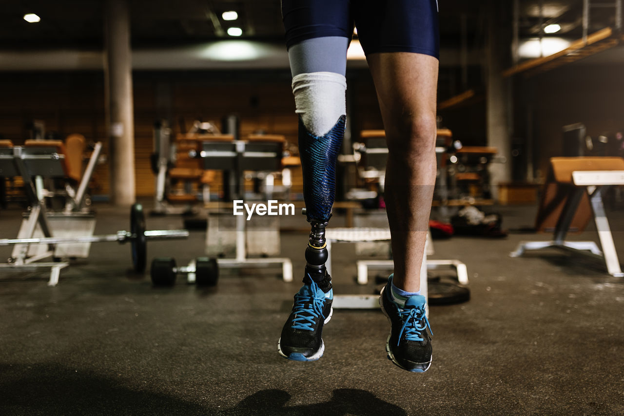 Low section of man with prosthetic leg jumping in gym