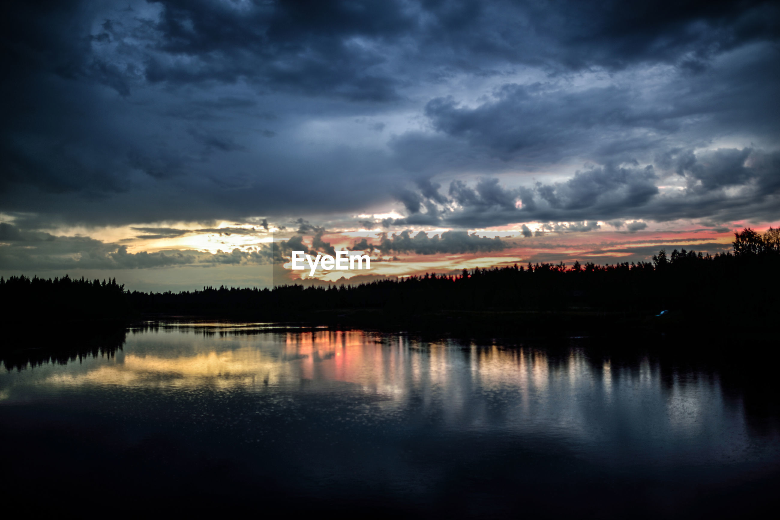 SCENIC VIEW OF LAKE BY SILHOUETTE TREES AGAINST SKY DURING SUNSET