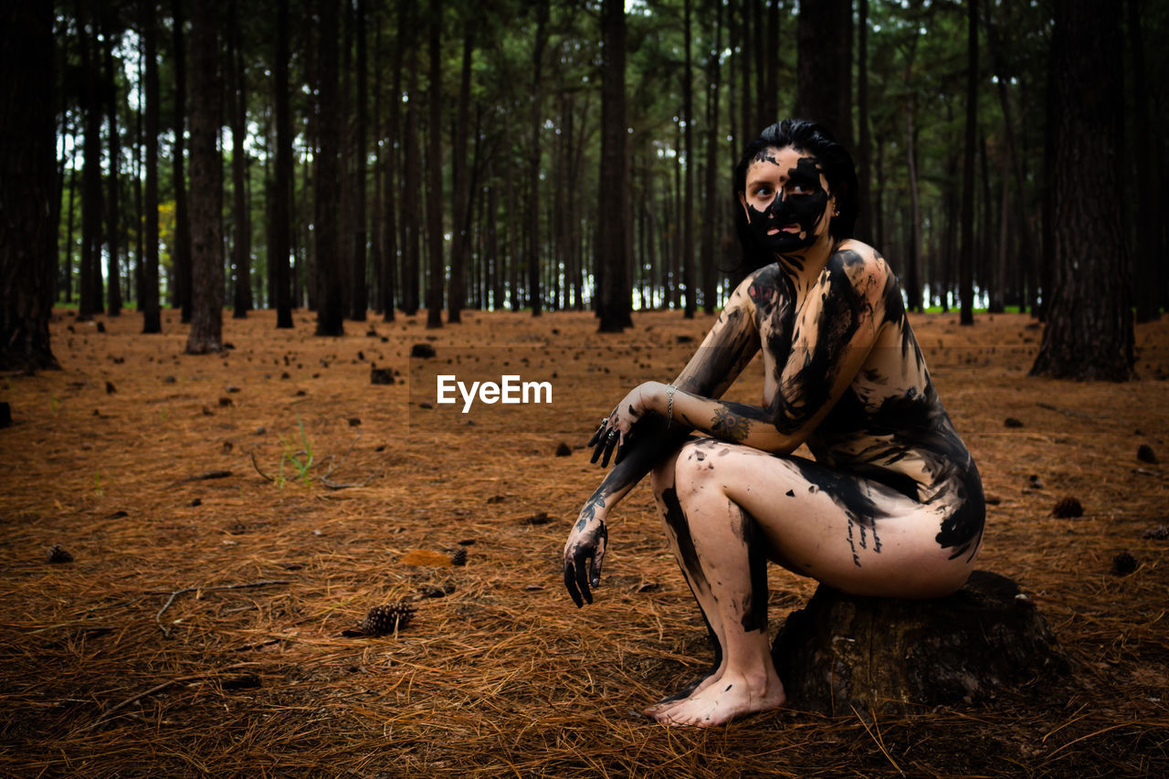 Portrait of naked woman covered with paint while sitting in forest