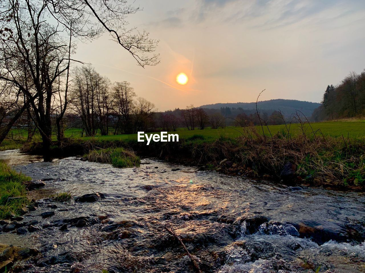 sky, water, scenics - nature, sunset, tranquil scene, beauty in nature, tree, tranquility, nature, plant, sun, no people, land, non-urban scene, cloud - sky, river, environment, landscape, rock, outdoors, flowing water, stream - flowing water, lens flare, flowing