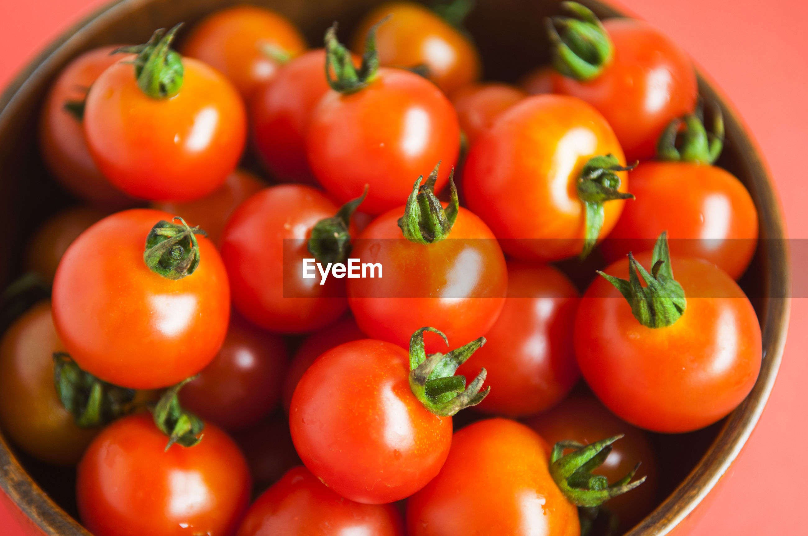 Close-up of tomatoes in bowl against red background
