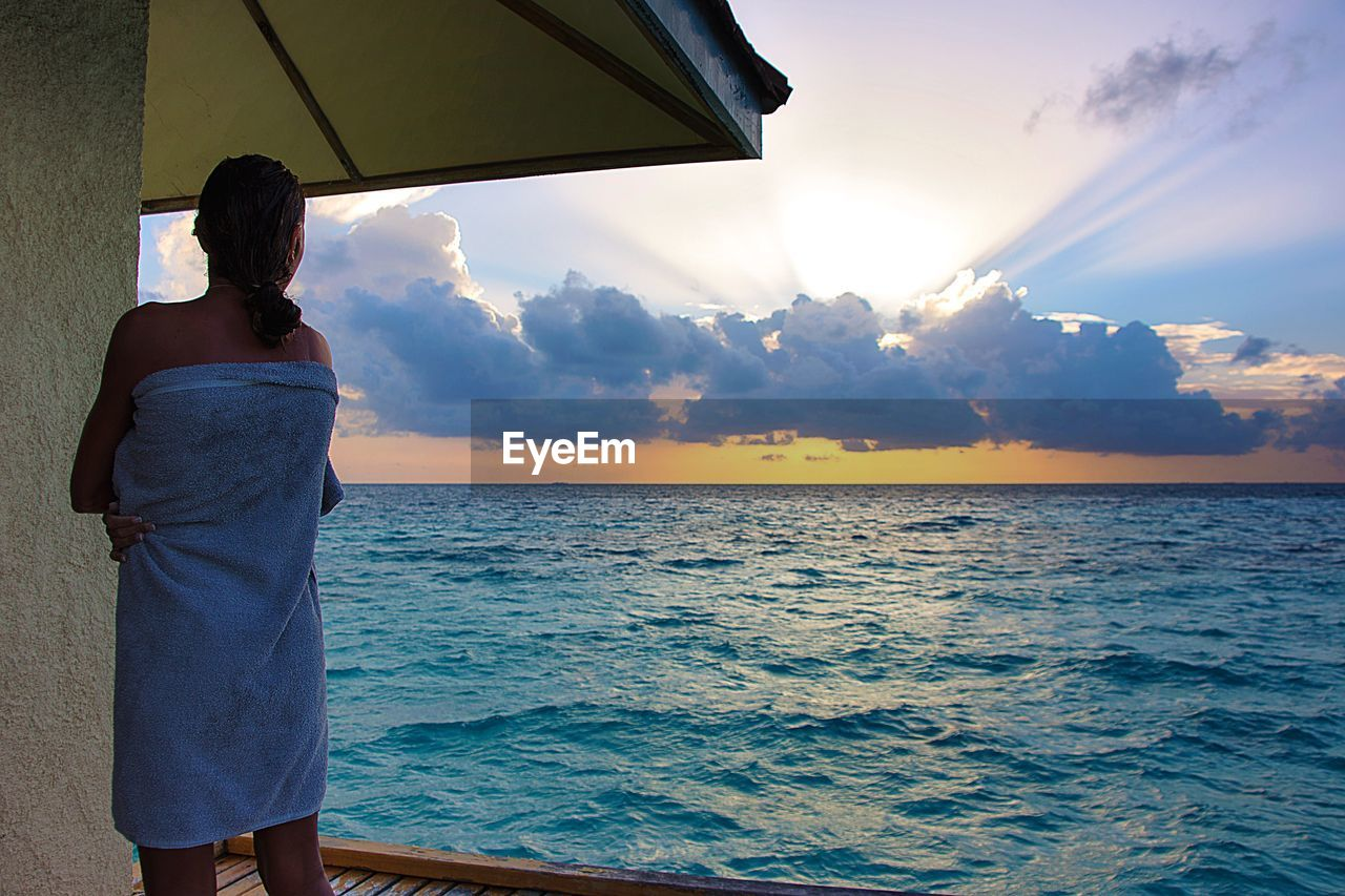 Rear View Of Woman Wrapped In Towel Standing By Sea During Sunset