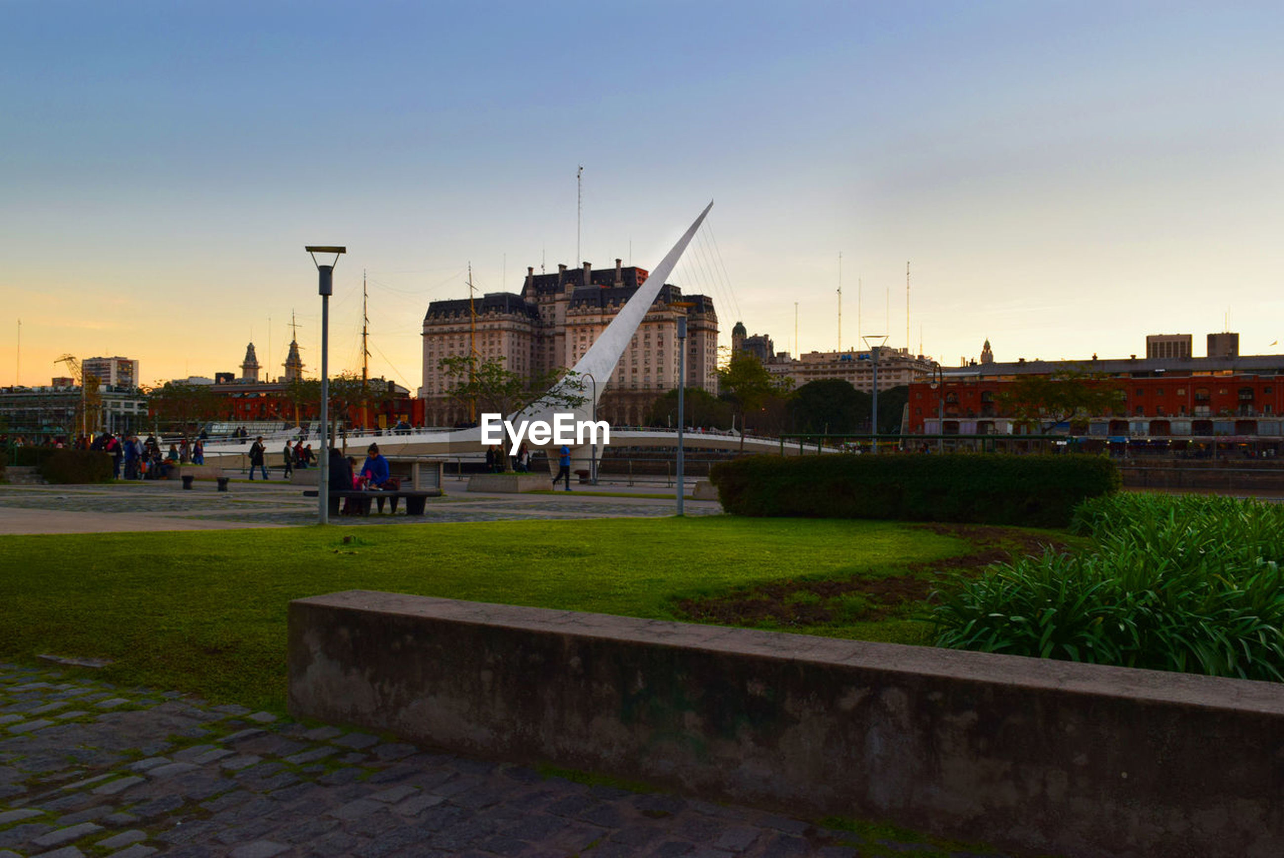 architecture, built structure, building exterior, travel destinations, city, sky, outdoors, sunset, nature, cityscape, grass, day, clear sky, large group of people, real people, water, people