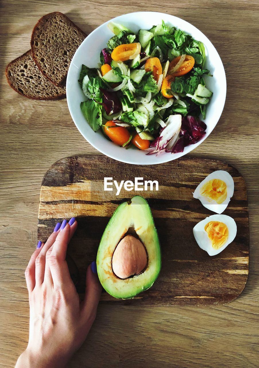 food and drink, food, healthy eating, freshness, hand, human hand, table, one person, wellbeing, real people, human body part, vegetable, fruit, indoors, high angle view, ready-to-eat, unrecognizable person, personal perspective, holding, body part, finger, breakfast
