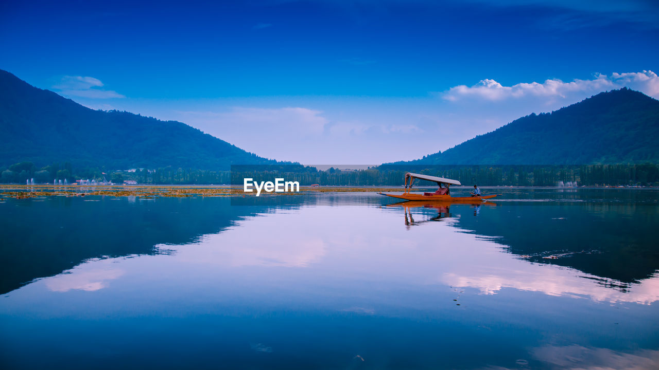 water, mountain, sky, scenics - nature, reflection, tranquility, tranquil scene, beauty in nature, cloud - sky, blue, nautical vessel, lake, waterfront, mountain range, transportation, nature, mode of transportation, non-urban scene, day, no people, outdoors, mountain peak