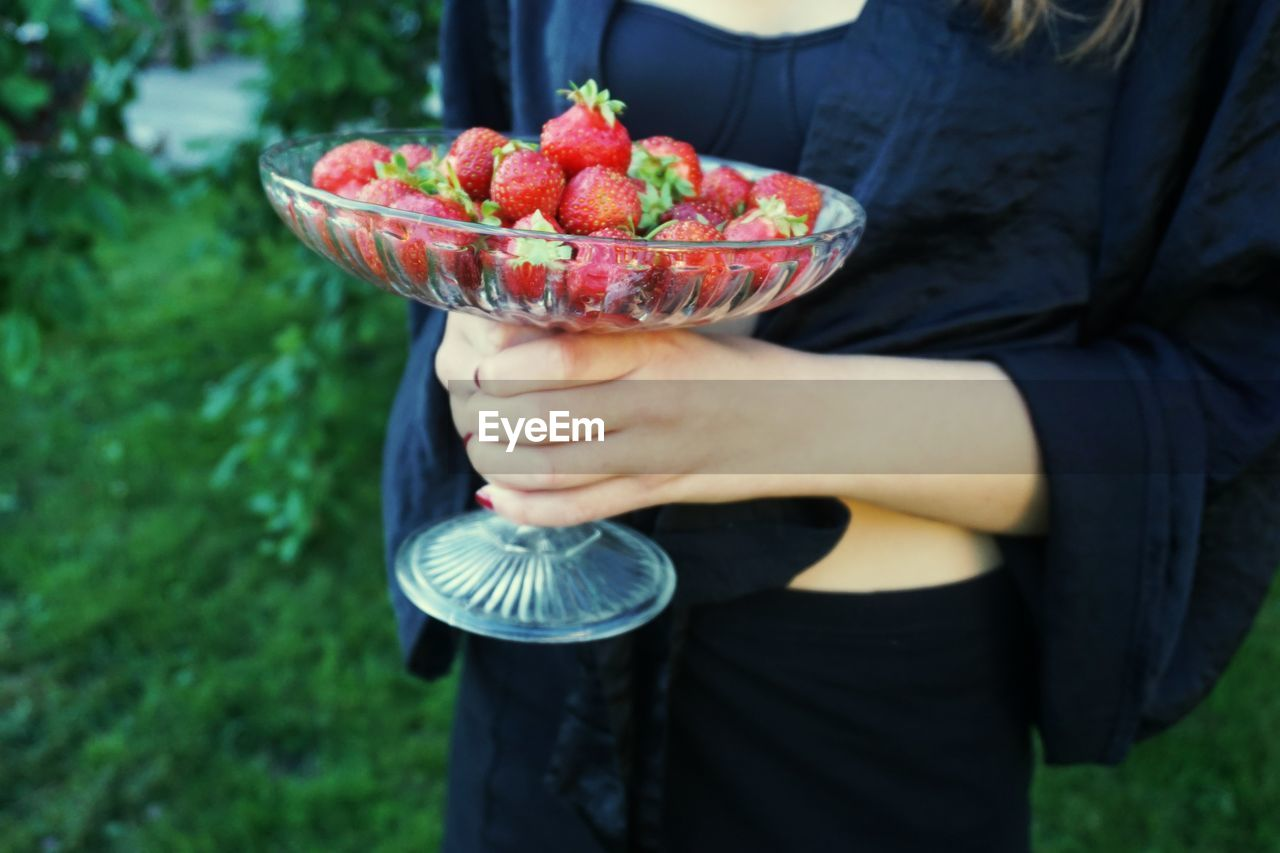 Midsection Of Woman Holding Strawberries