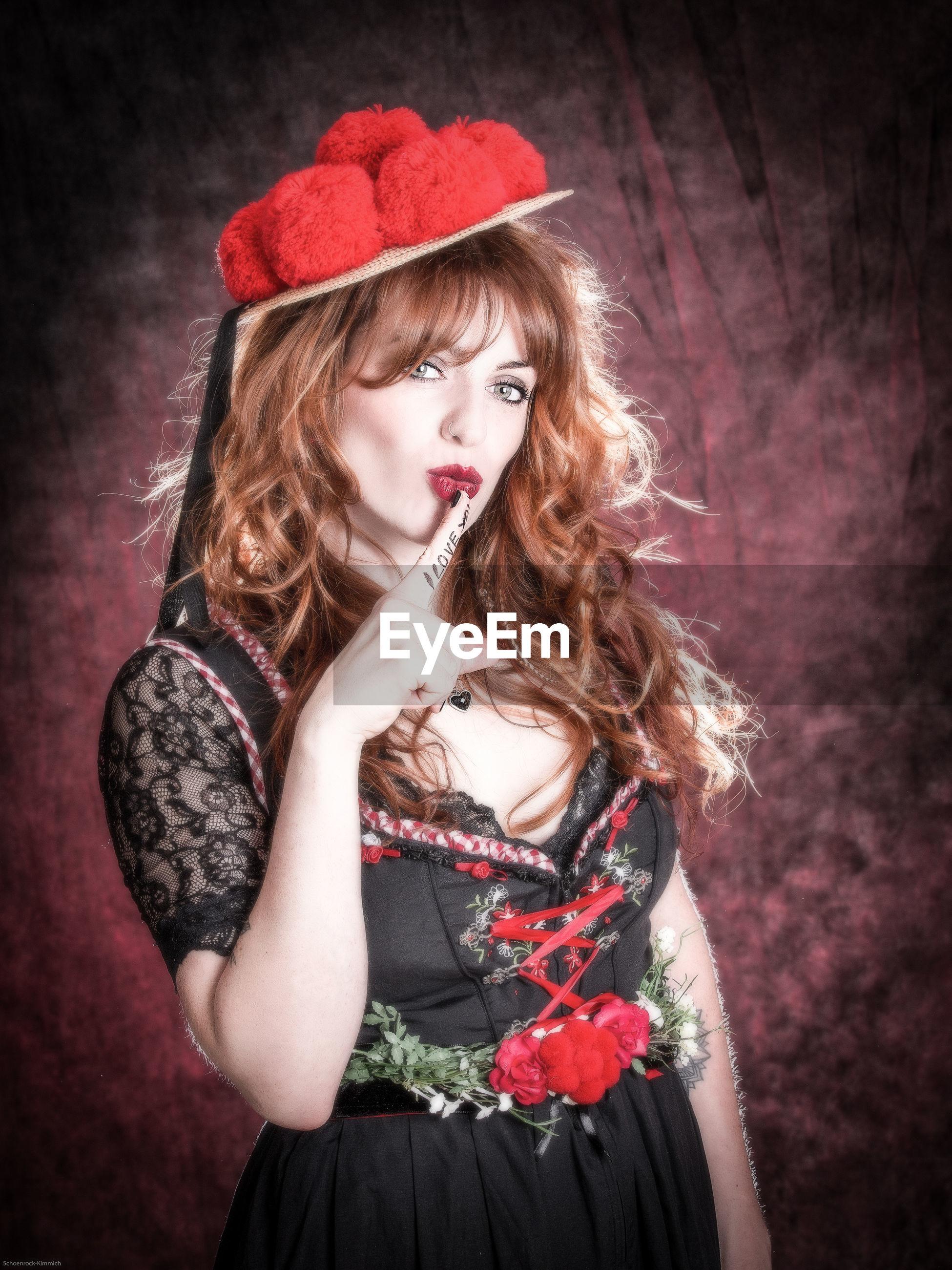 Portrait of beautiful woman showing finger on lips