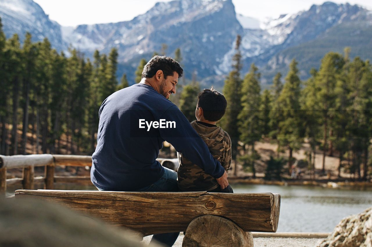 Father and son sitting by lake against mountain