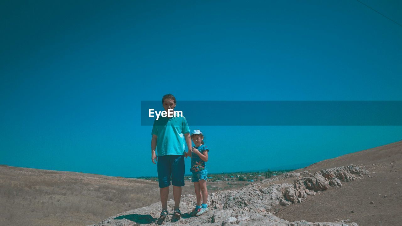 blue, togetherness, clear sky, copy space, full length, casual clothing, boys, two people, day, childhood, leisure activity, outdoors, real people, bonding, looking at camera, elementary age, love, standing, portrait, nature, happiness, sky, people