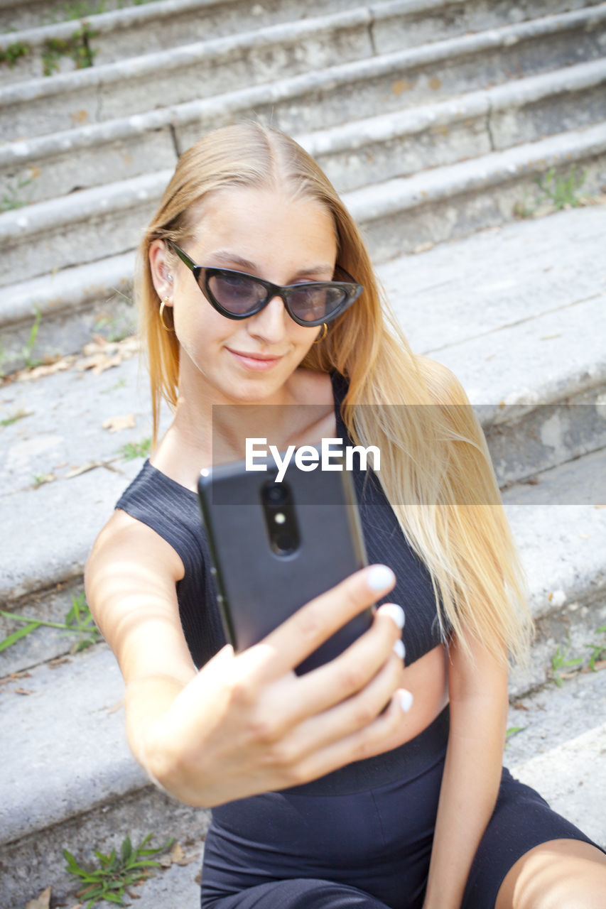 wireless technology, technology, mobile phone, glasses, young adult, one person, real people, lifestyles, portable information device, smart phone, leisure activity, connection, young women, communication, front view, holding, three quarter length, telephone, using phone, day, hair, fashion, outdoors, hairstyle