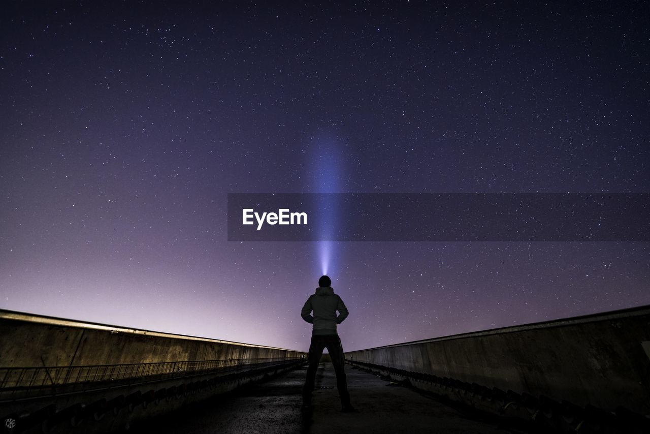 Man standing on bridge against sky at night