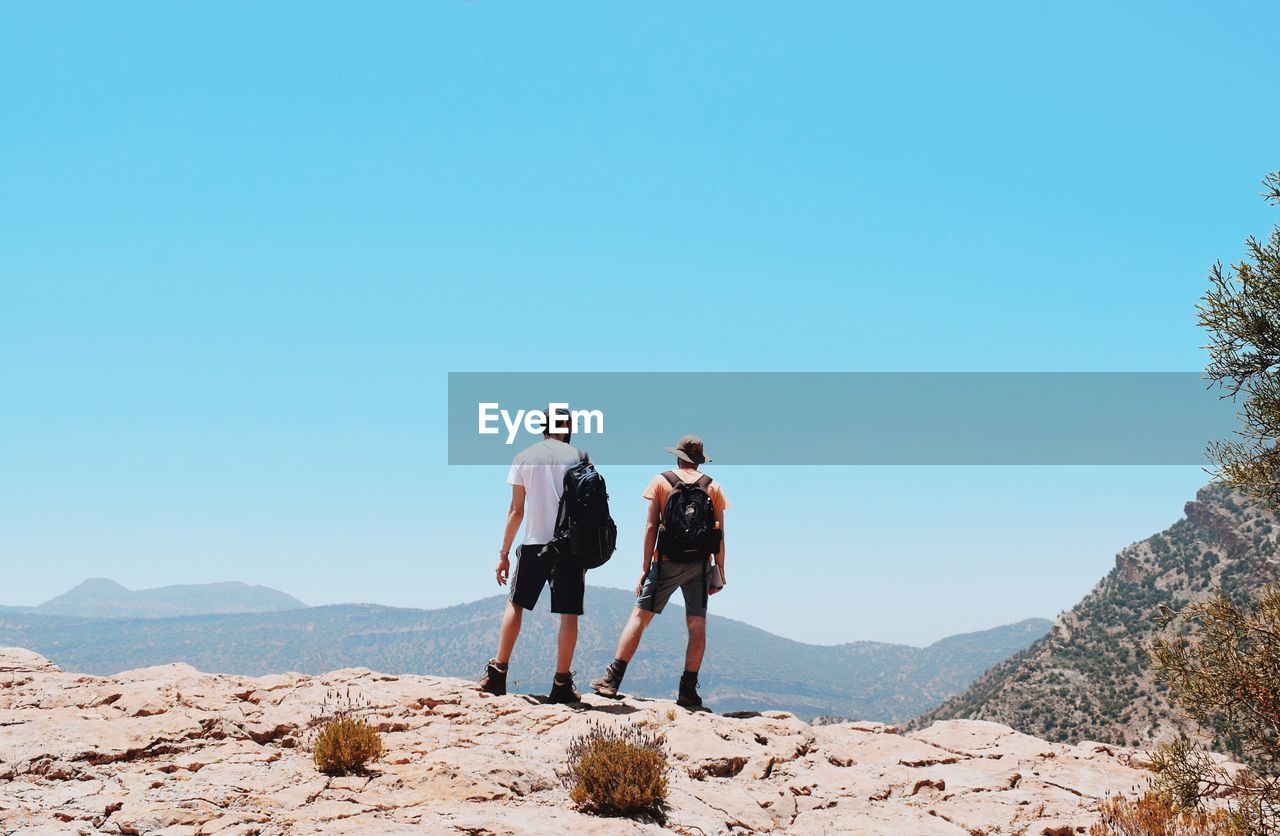 sky, leisure activity, clear sky, rear view, real people, lifestyles, nature, copy space, mountain, togetherness, blue, men, beauty in nature, two people, day, hiking, sunlight, people, full length, rock, outdoors, couple - relationship