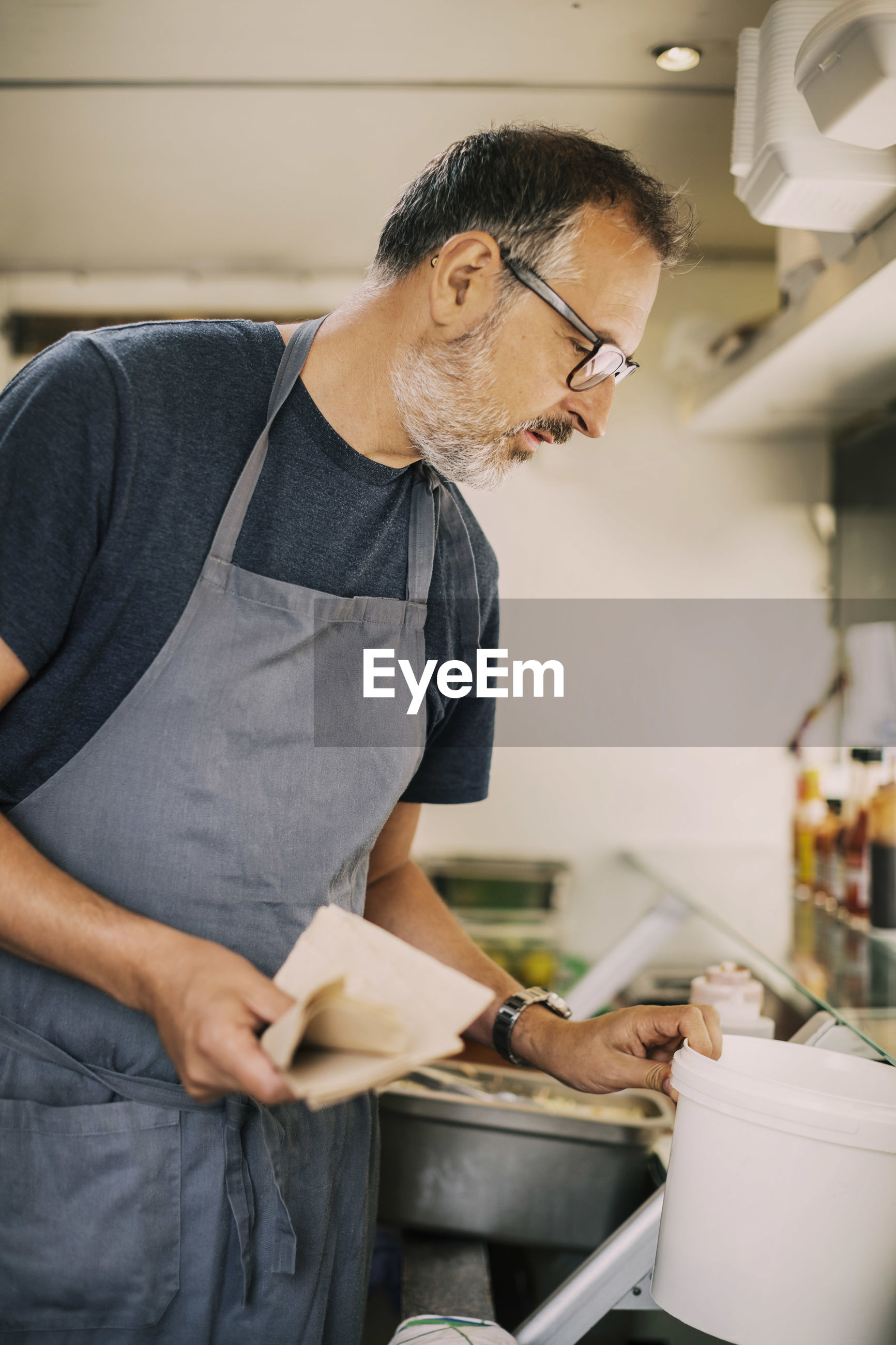 Mature chef working in kitchen of food truck