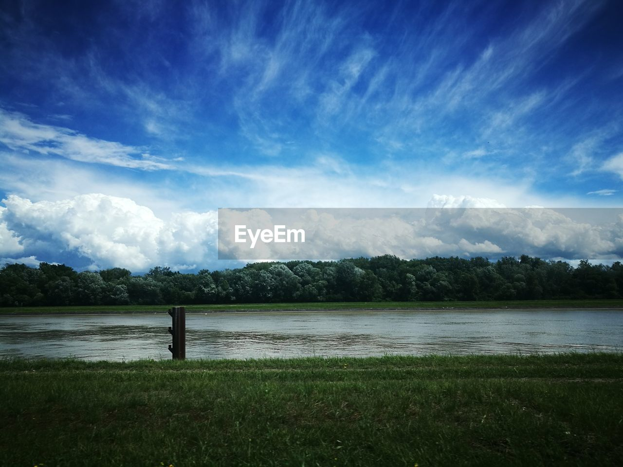 sky, lake, scenics, cloud - sky, tranquility, nature, water, beauty in nature, tranquil scene, no people, landscape, grass, outdoors, day, mountain, tree