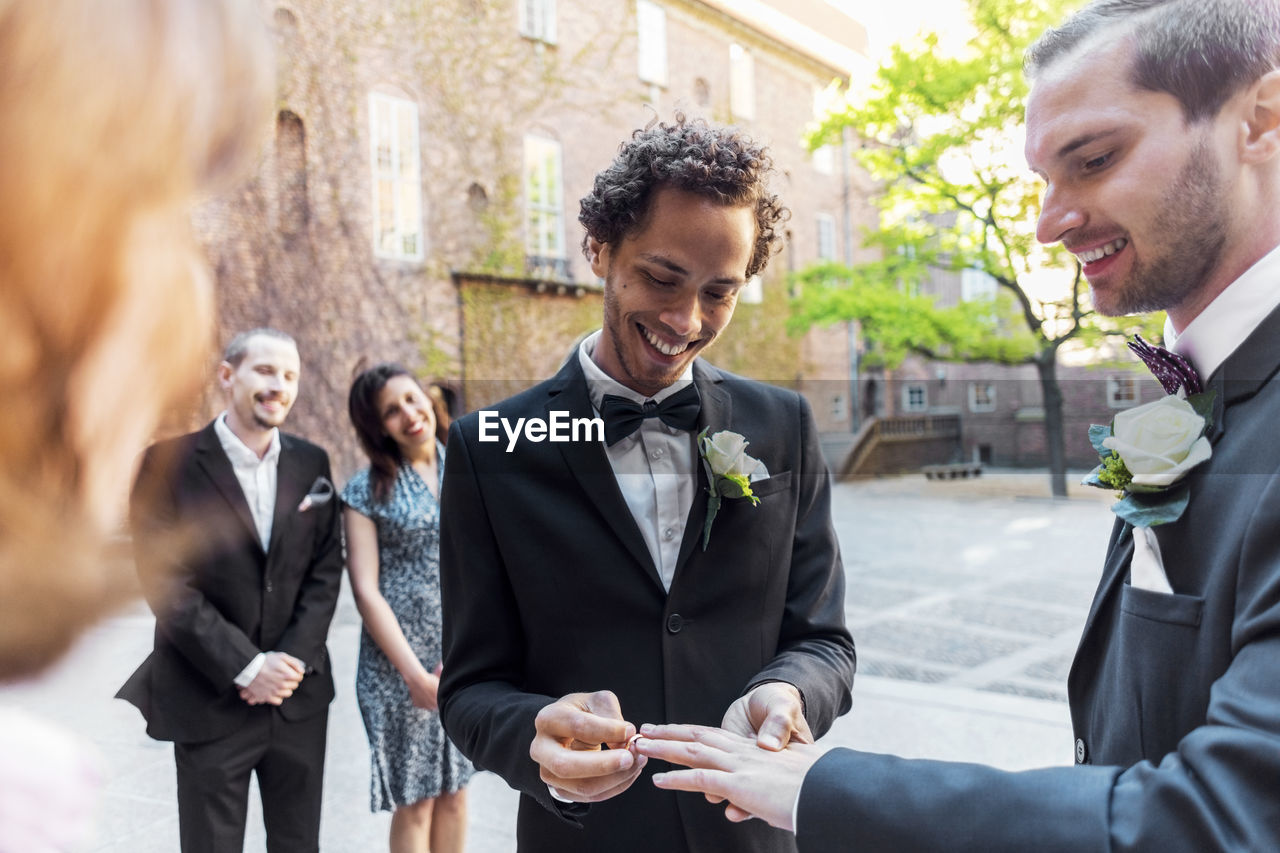 men, well-dressed, males, celebration, event, adult, smiling, group of people, young adult, emotion, formalwear, women, architecture, happiness, togetherness, suit, wedding, young men, bridegroom, wedding ceremony, mature men, positive emotion, couple - relationship, outdoors