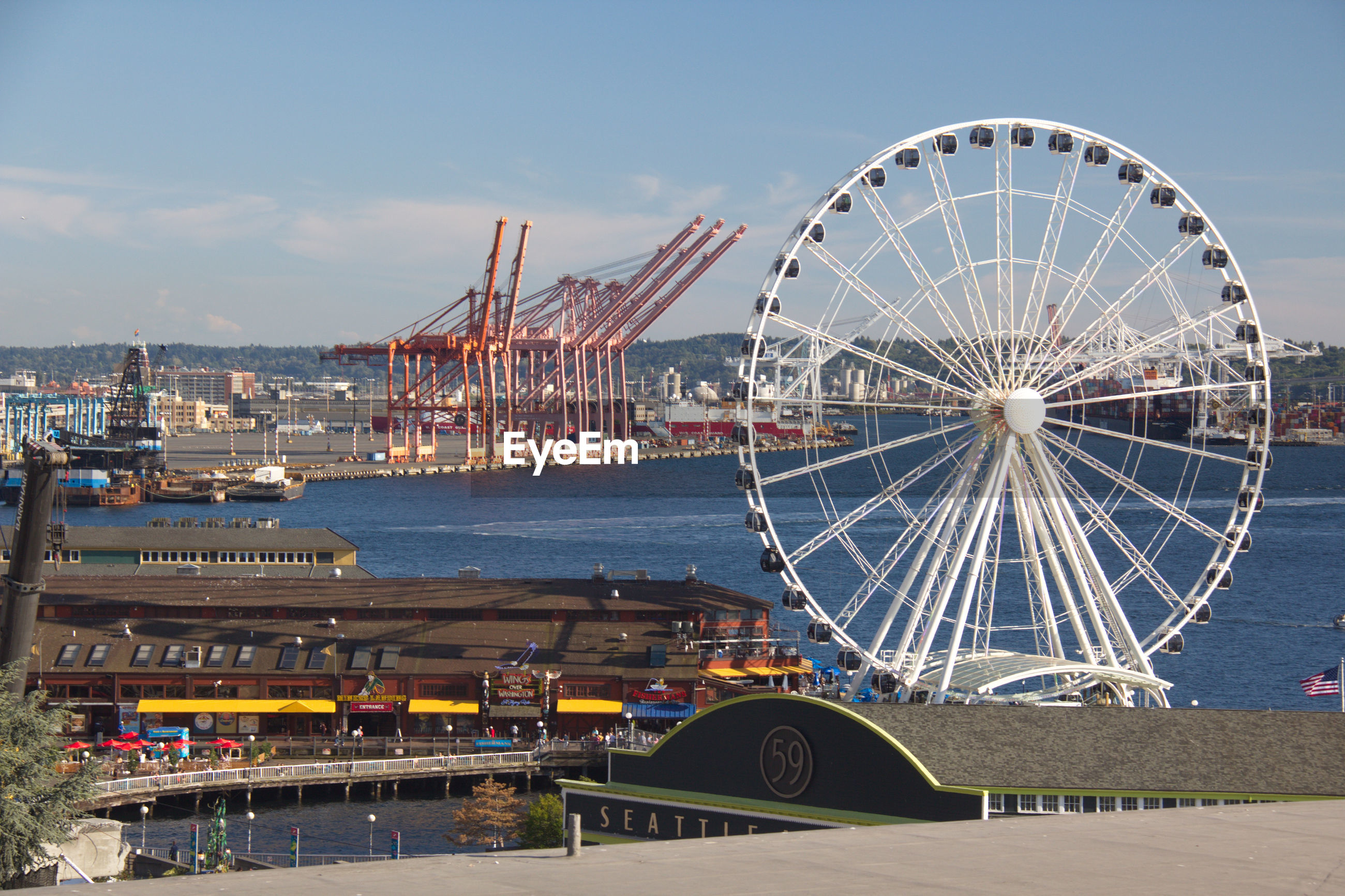 HIGH ANGLE VIEW OF FERRIS WHEEL BY CITY AGAINST SKY
