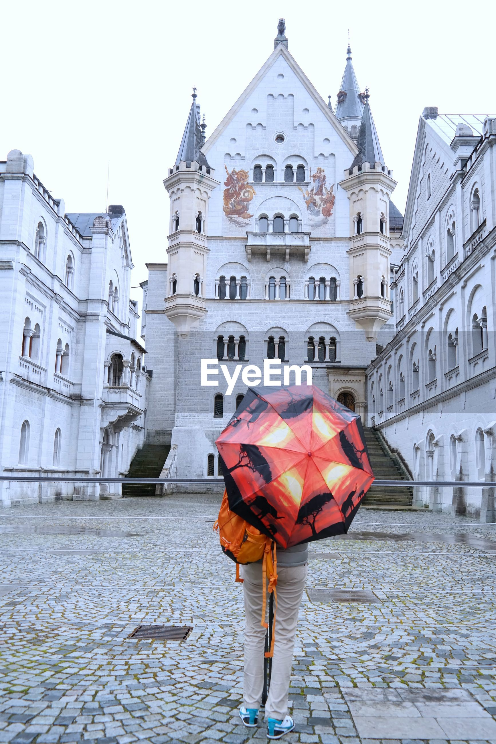 Rear view of person carrying umbrella in front of neuschwanstein castle