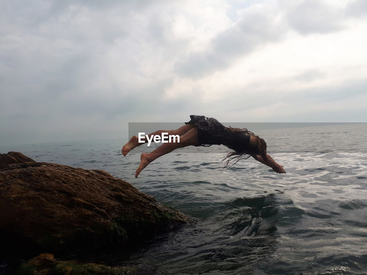 Woman jumping on rock in sea against sky