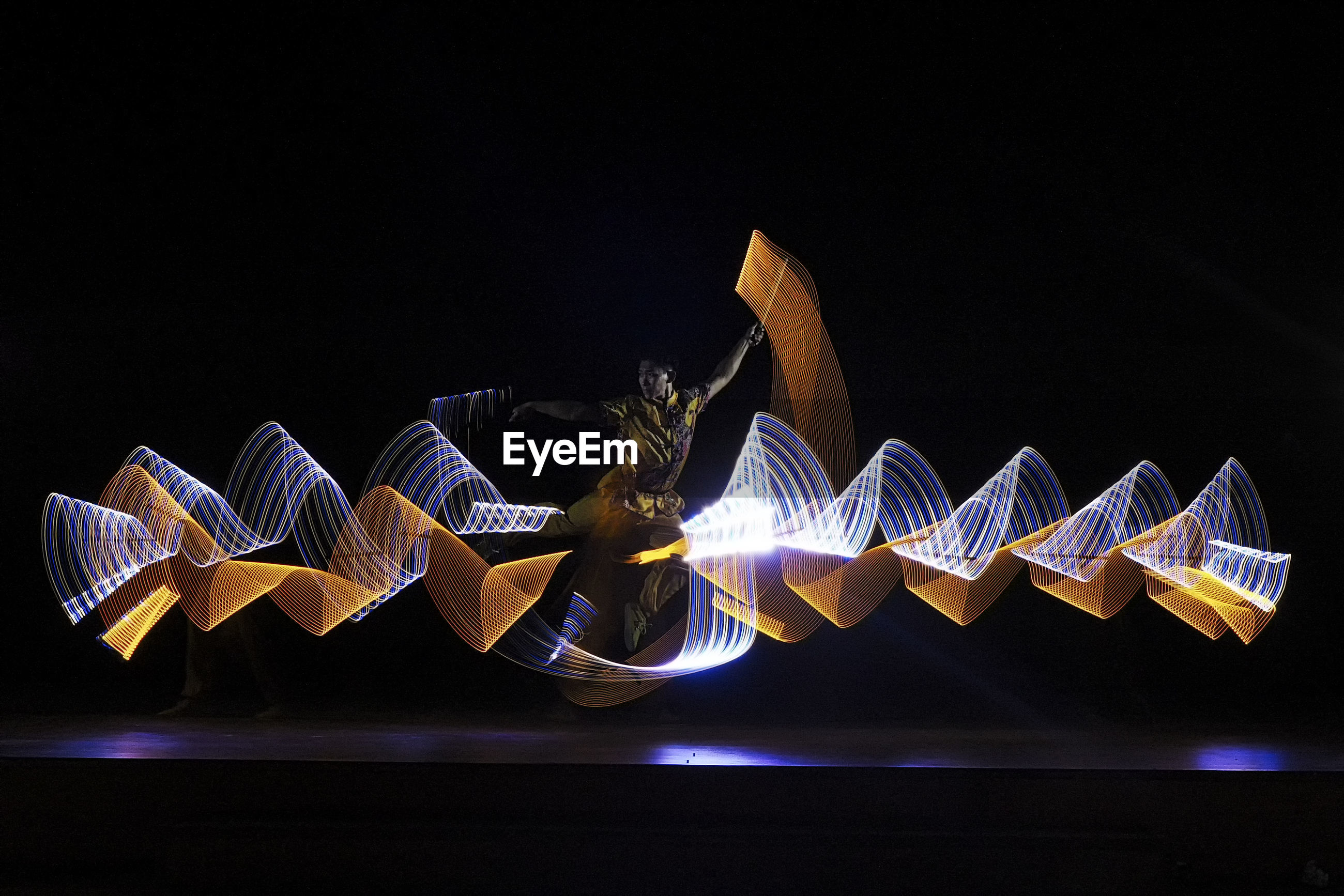 Man with light painting performing on stage
