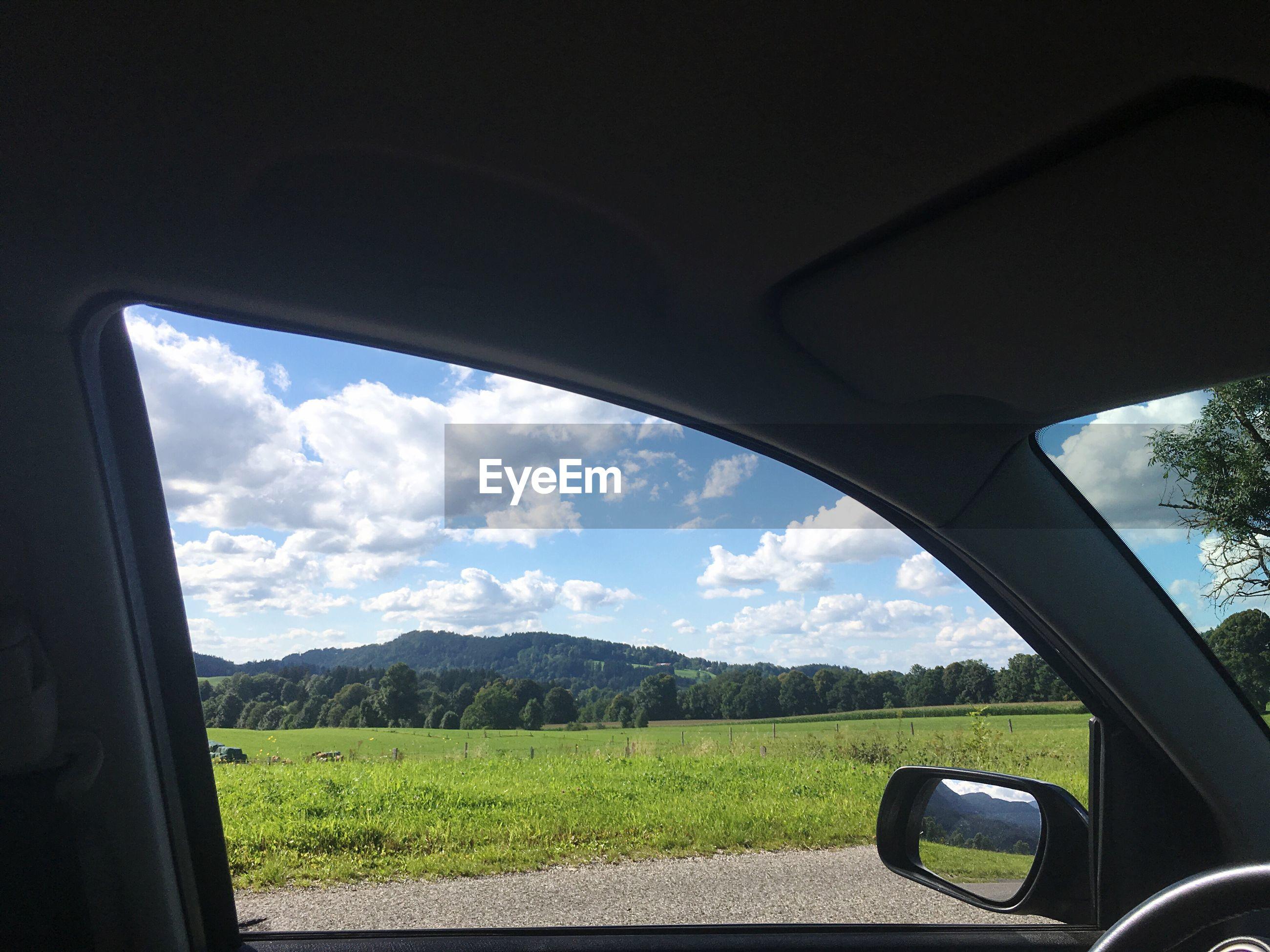 Green landscape against sky seen through car window