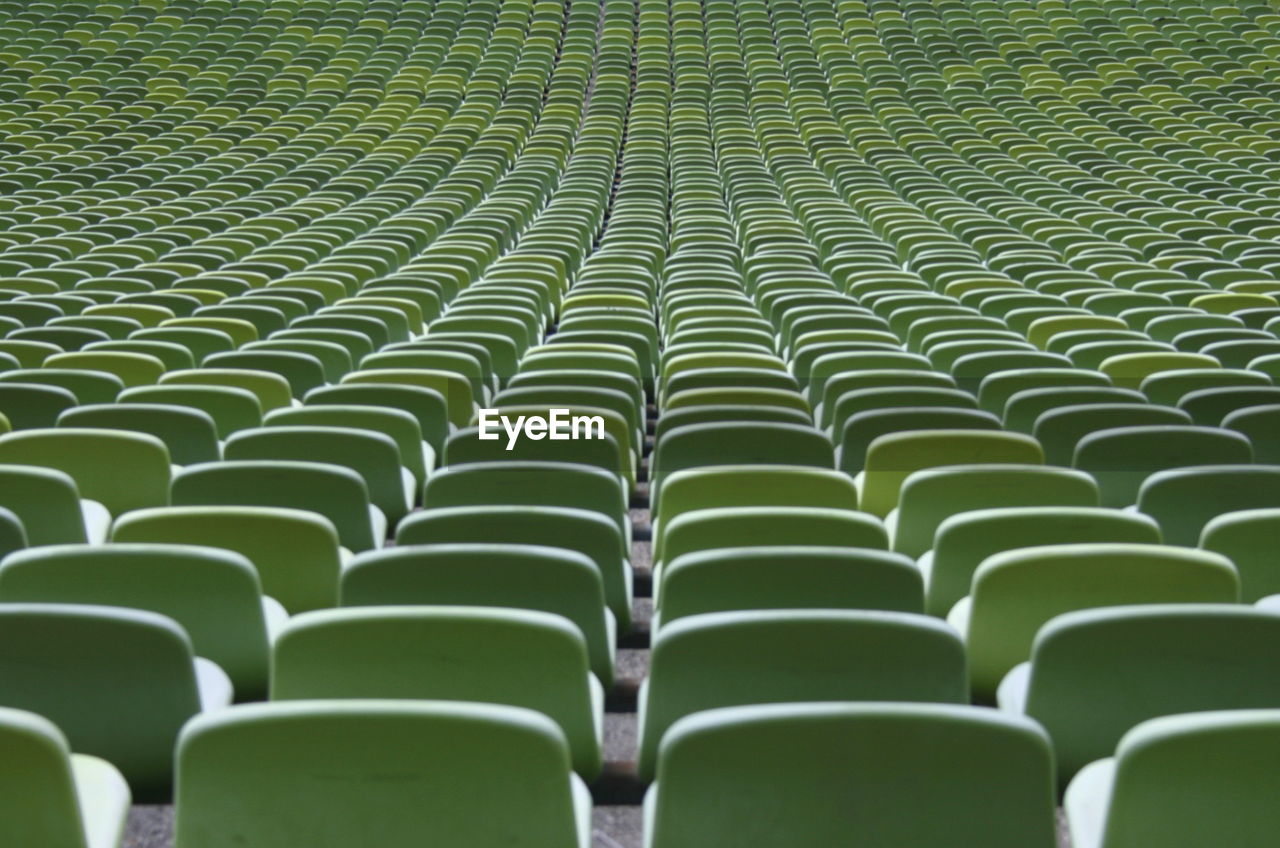 in a row, backgrounds, full frame, repetition, seat, empty, green color, no people, absence, pattern, side by side, chair, large group of objects, stadium, abundance, bleachers, sport, order, day, arrangement