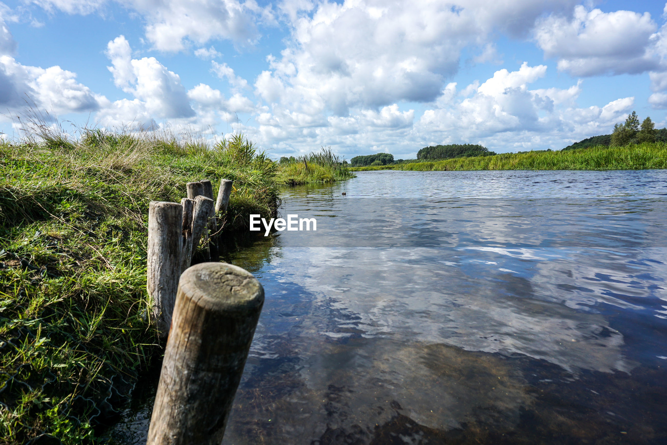 Wooden post in a river against cloudy sky