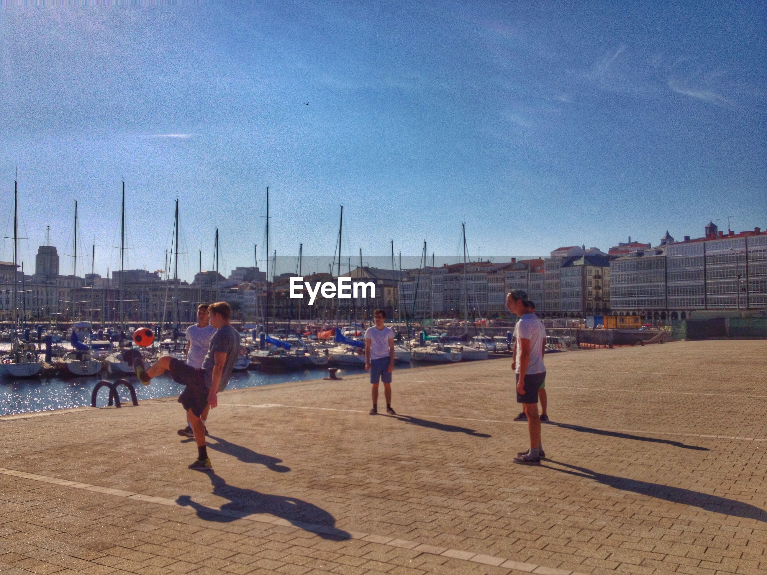 building exterior, architecture, built structure, sky, city, beach, sand, men, lifestyles, leisure activity, person, water, sunlight, city life, full length, sea, incidental people, large group of people, walking