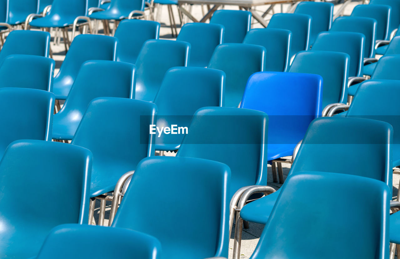 seat, chair, empty, in a row, repetition, blue, side by side, large group of objects, absence, no people, full frame, arrangement, backgrounds, auditorium, arts culture and entertainment, order, stadium, indoors, abundance, sport, foldable