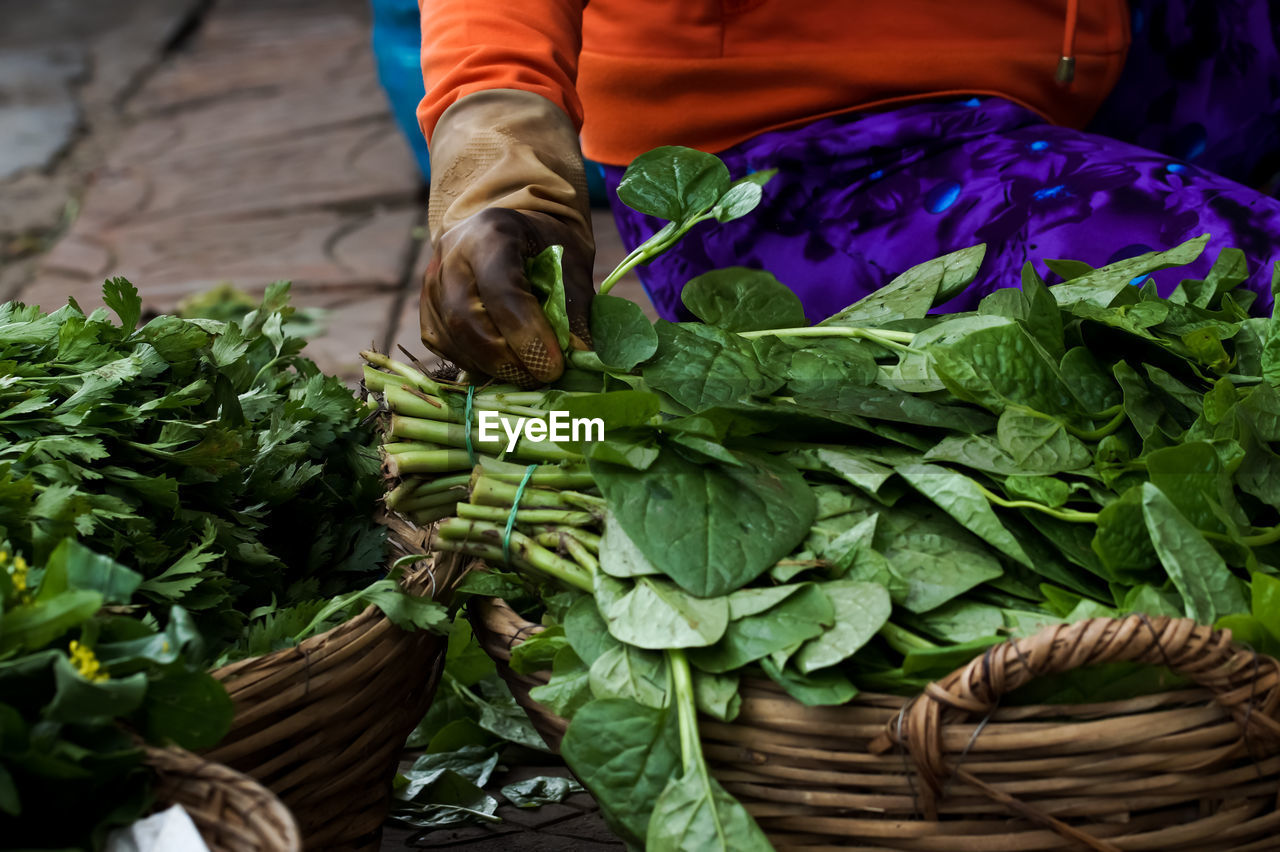 Midsection Of Vendor Selling Spinach At Market