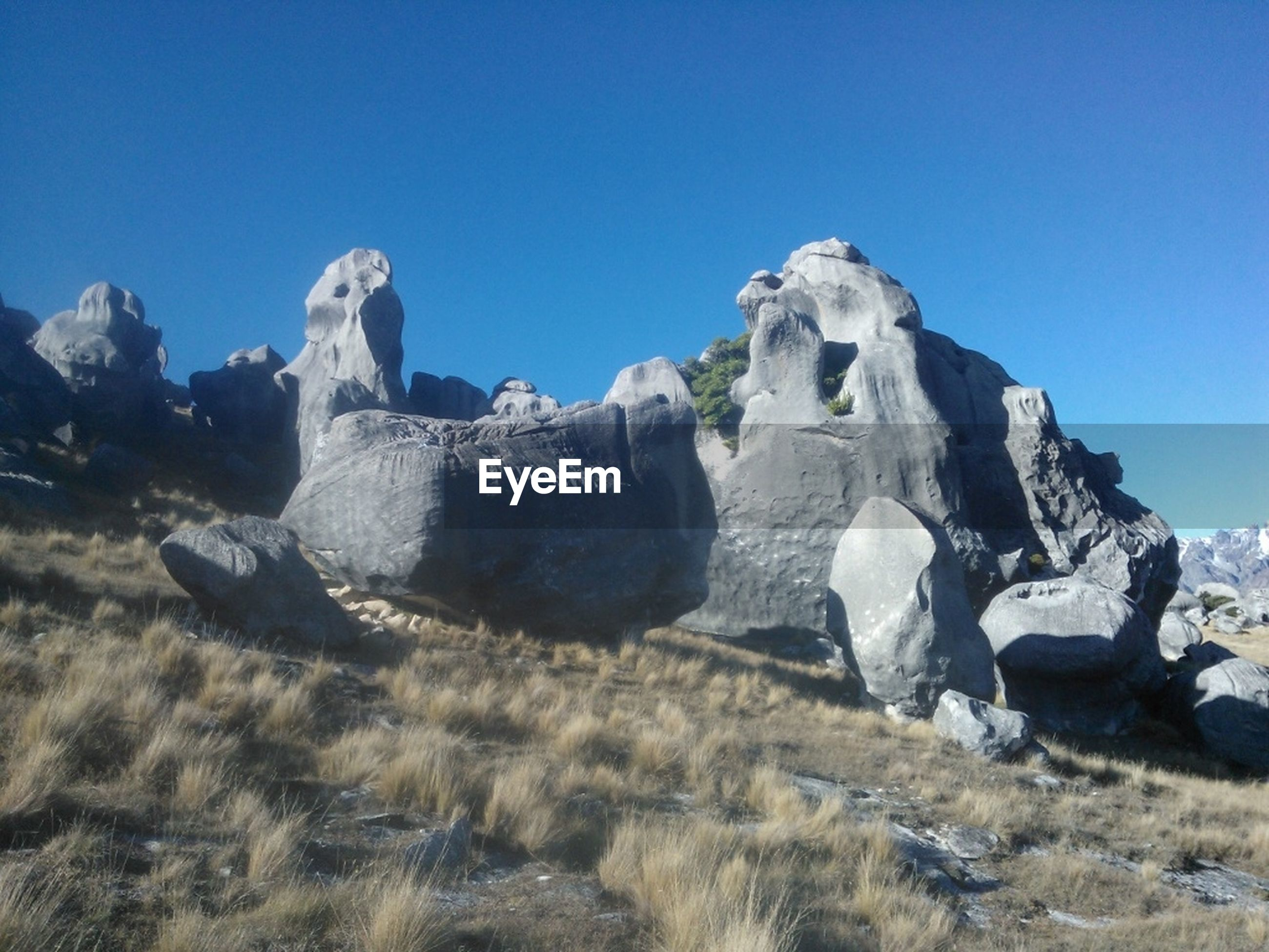 clear sky, blue, copy space, rock formation, rock - object, tranquility, tranquil scene, scenics, nature, beauty in nature, geology, sunlight, landscape, rock, eroded, non-urban scene, day, physical geography, travel destinations, low angle view