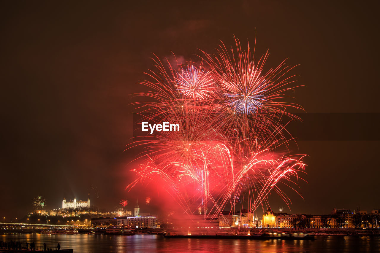 night, firework display, illuminated, celebration, firework - man made object, exploding, arts culture and entertainment, building exterior, river, built structure, sky, event, architecture, waterfront, water, no people, city, outdoors, motion, cityscape, firework, multi colored