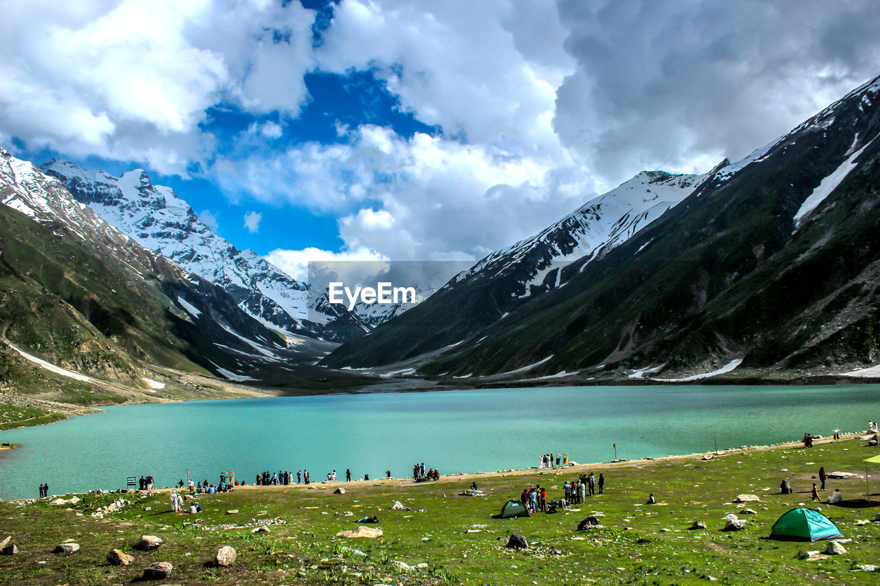 mountain, water, sky, cloud - sky, beauty in nature, scenics - nature, nature, lake, environment, landscape, day, cold temperature, grass, tranquil scene, snow, mountain range, tranquility, non-urban scene, outdoors, snowcapped mountain