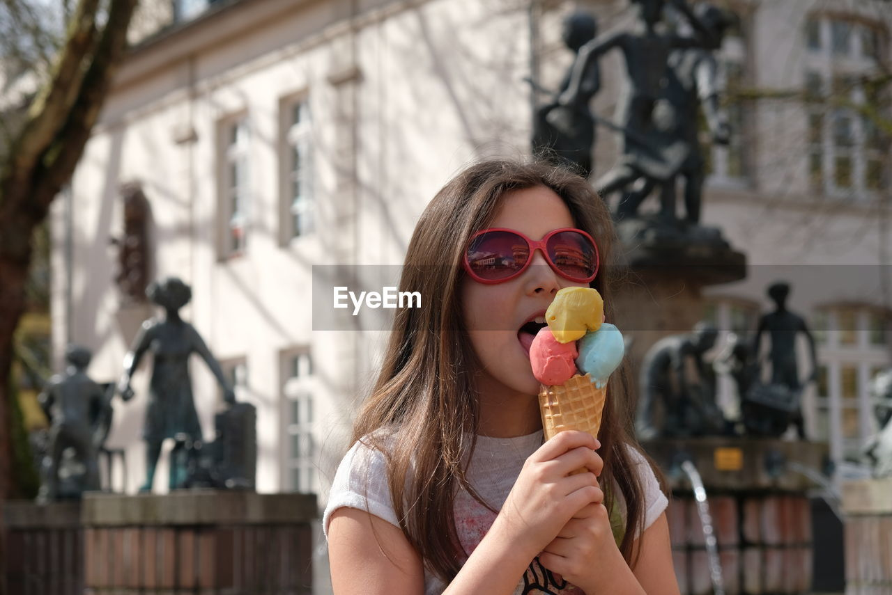 Girl eating ice cream cone in city