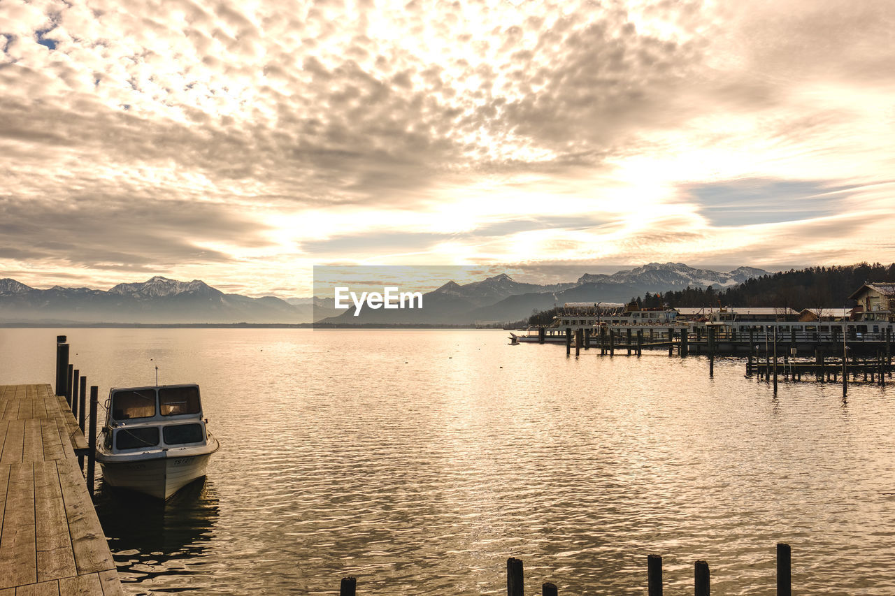 sky, nautical vessel, cloud - sky, water, transportation, mode of transportation, beauty in nature, sunset, scenics - nature, mountain, tranquil scene, tranquility, no people, moored, nature, reflection, lake, idyllic, mountain range, outdoors, wooden post, bay