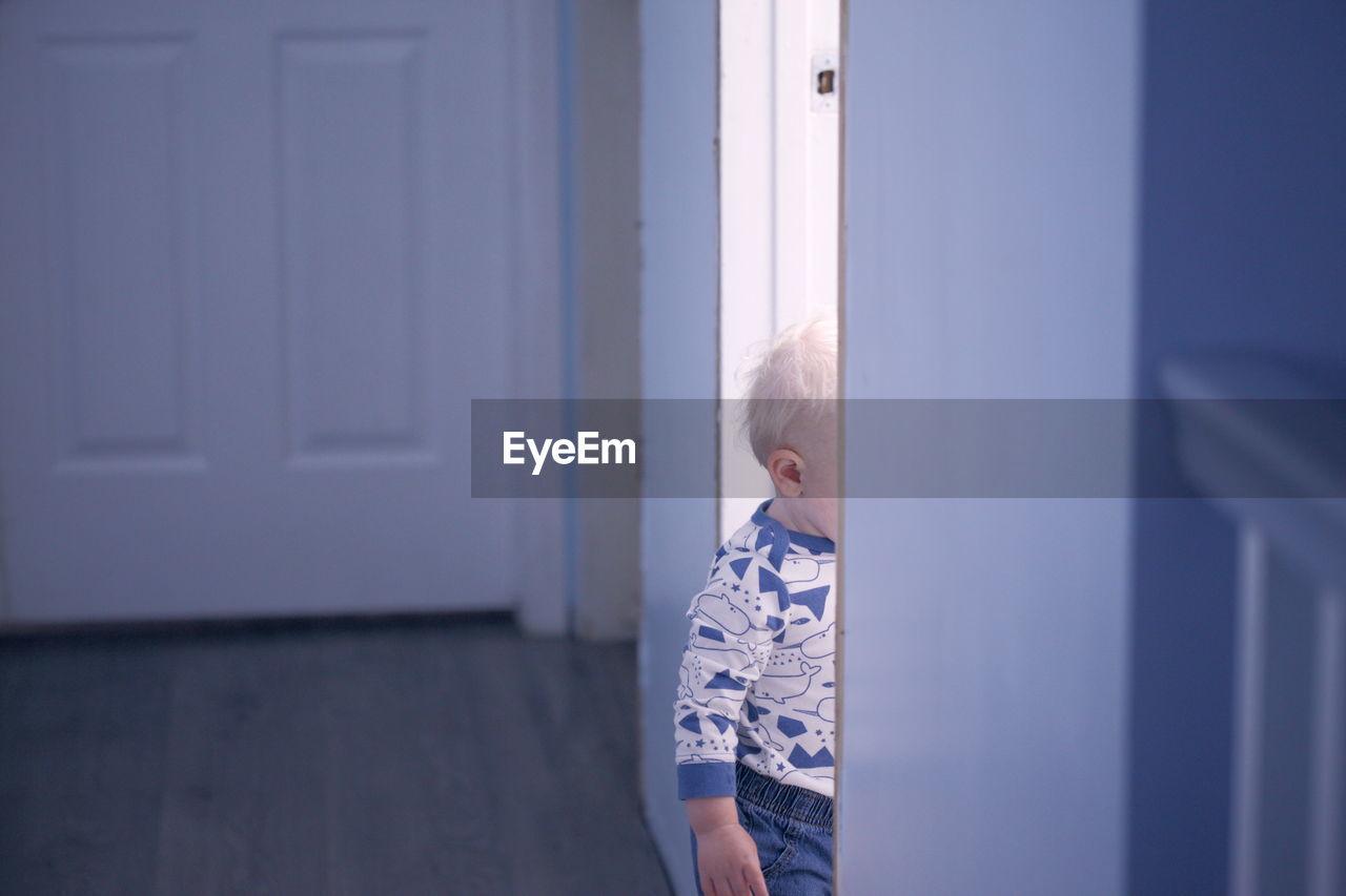 Cute Boy Standing At Entrance Door