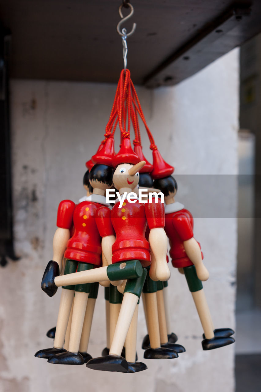 human representation, representation, red, art and craft, indoors, no people, male likeness, figurine, focus on foreground, still life, creativity, toy, wood - material, hanging, craft, female likeness, close-up, sculpture, sport, table