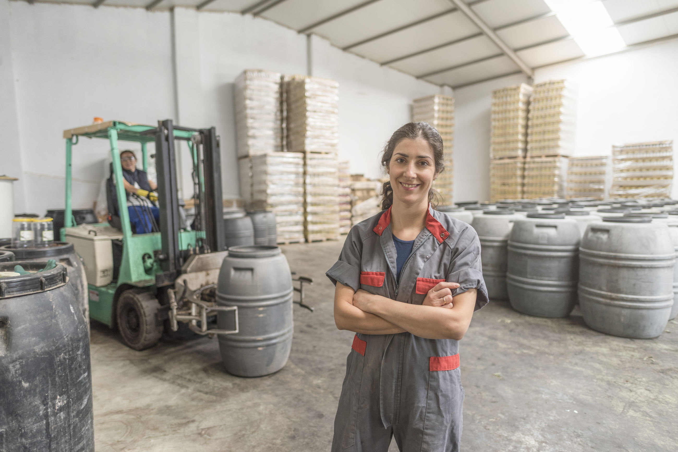 Portrait of female worker with arms crossed standing at warehouse
