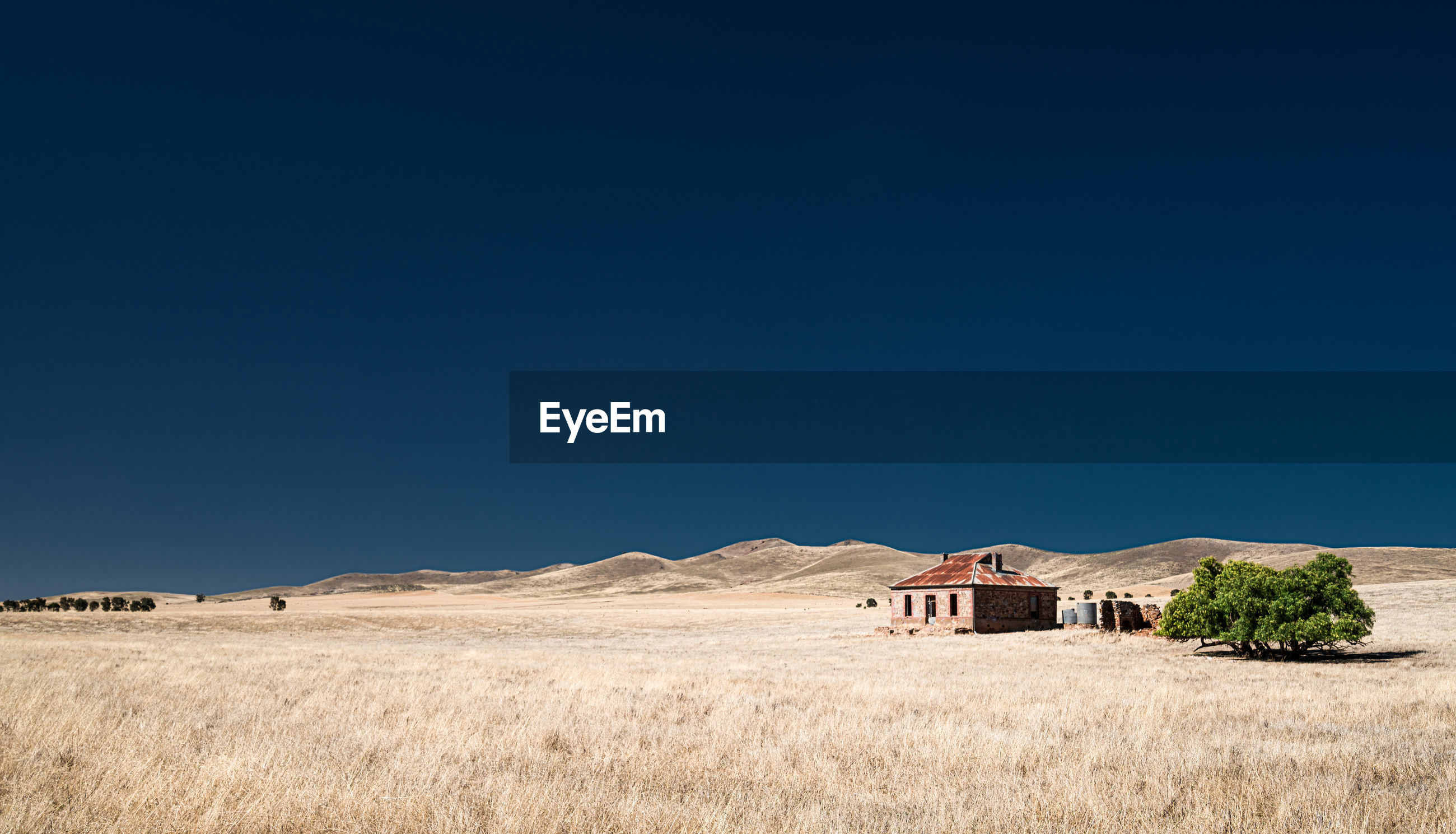 HOUSE ON FIELD AGAINST BLUE SKY